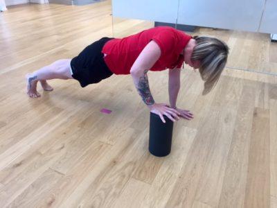 Frau im Fitnessraum während einer Übung mit der Blackroll